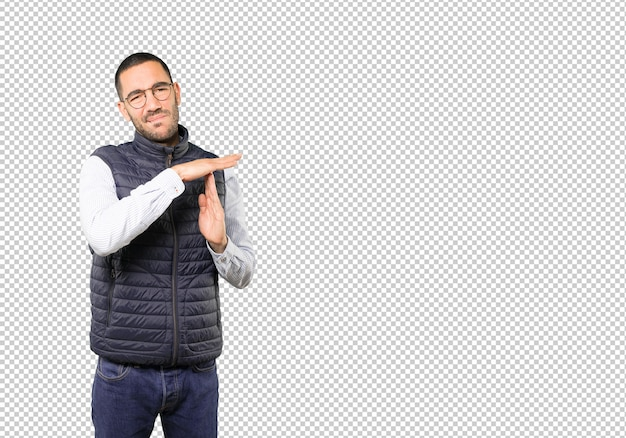 Stressed young man making a time out gesture with his hands Premium Psd