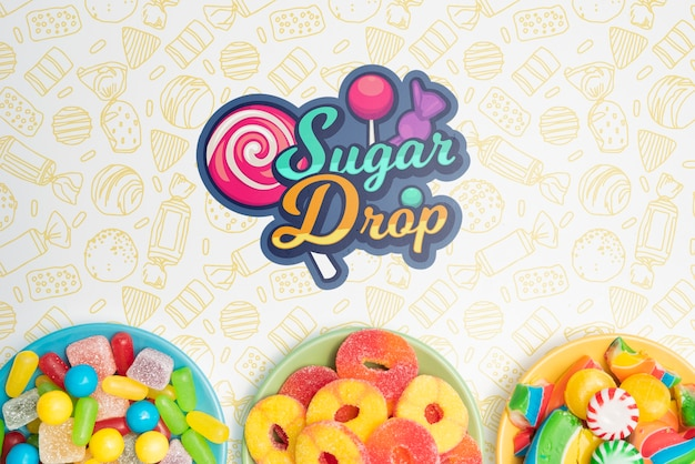Sugar drop and plates with delicious assortments of candies Free Psd