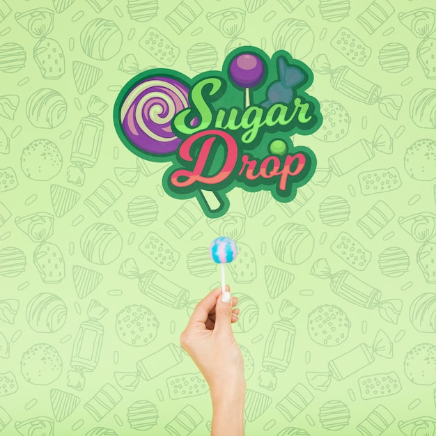 Sugar drop with hand and doodle green background Free Psd