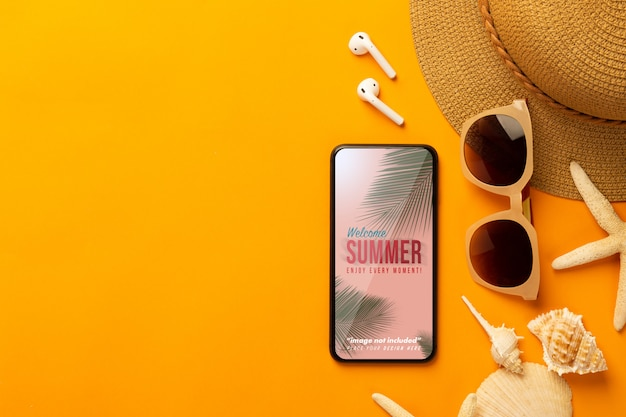 Summer background with phone mockup template and beach accessories on vibrant orange background Premium Psd