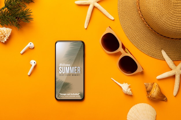 Summer background with phone mockup template and beach accessories on vibrant orange Premium Psd