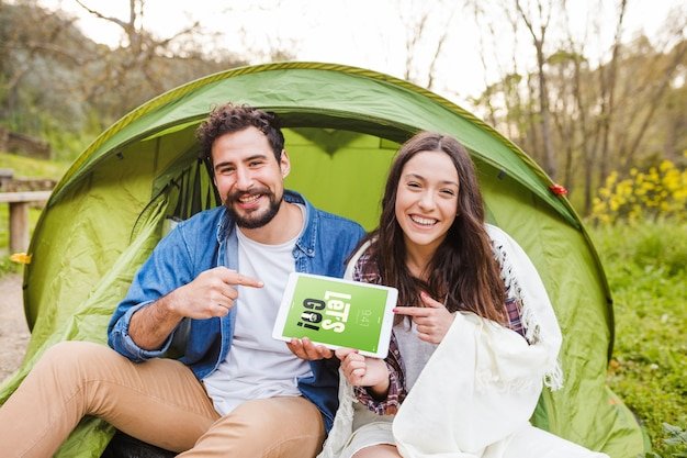 Summer camp mockup with couple pointing at tablet Free Psd