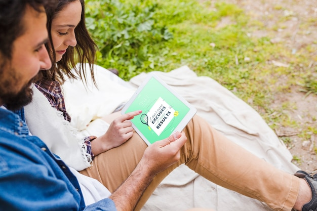 Summer camp mockup with couple using tablet Free Psd