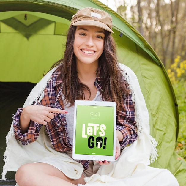 Summer camp mockup with woman pointing at tablet Free Psd