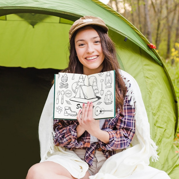 Summer camp mockup with woman showing open book Free Psd