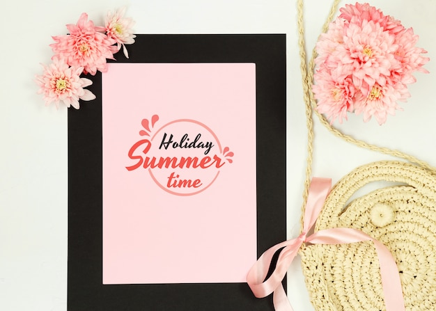 Summer composition with black frame, pink flowers and straw bag on white background Premium Psd