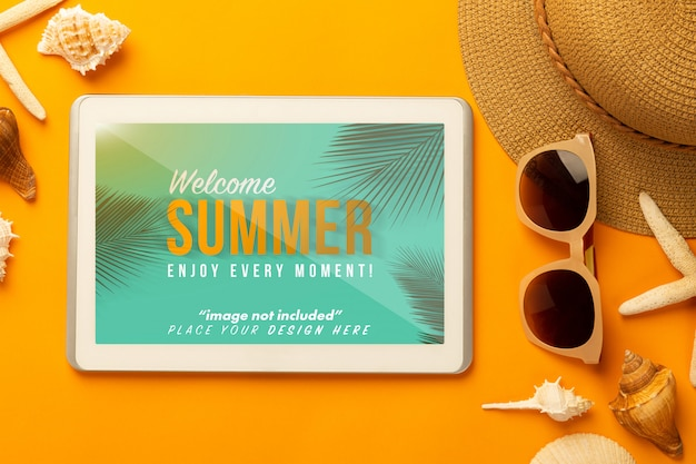 Summer composition with tablet mockup and beach accessories on orange surface Premium Psd