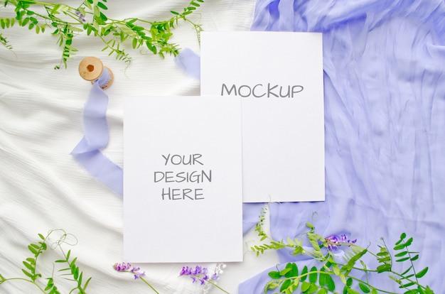 夏のひな形のモックアップグリーティングカードや紫の花と白の繊細なシルクのリボンの結婚式の招待状 Premium Psd