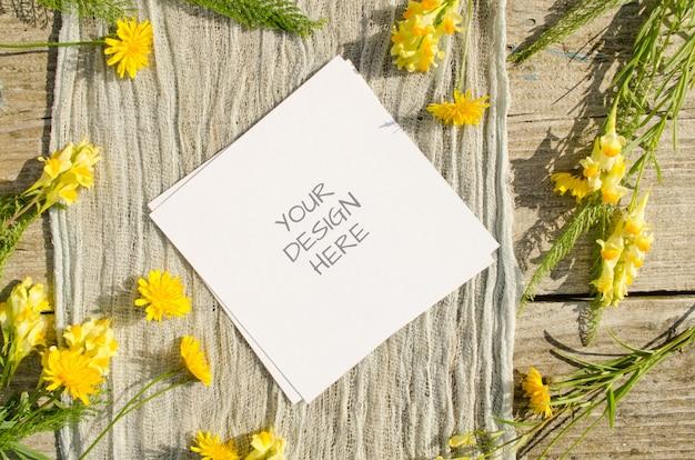 夏の文房具モックアップグリーティングカードまたは素朴なスタイルと自然の古い木製のスペースに黄色い花を持つ結婚式の招待状 Premium Psd