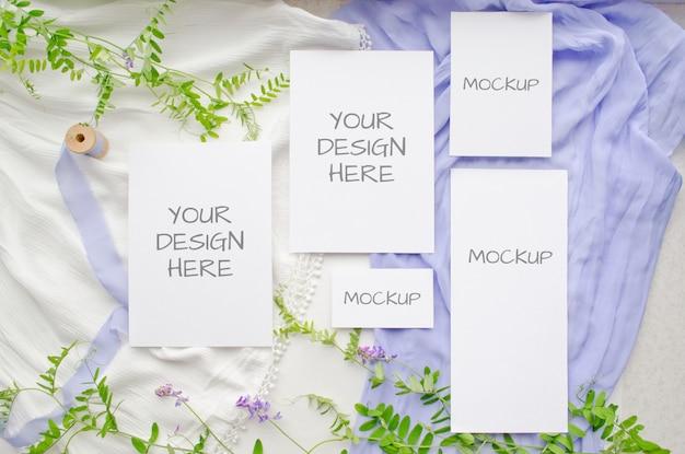 夏の文房具の結婚式のモックアップは紫の花と白の繊細なシルクのリボンでカードを設定 Premium Psd