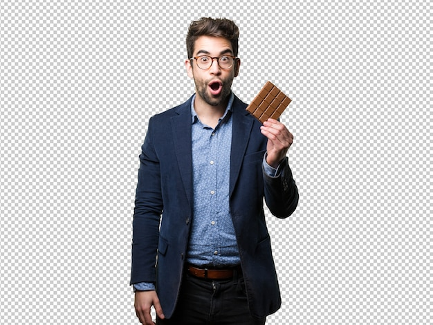 Surprised young man holding a chocolate bar Premium Psd