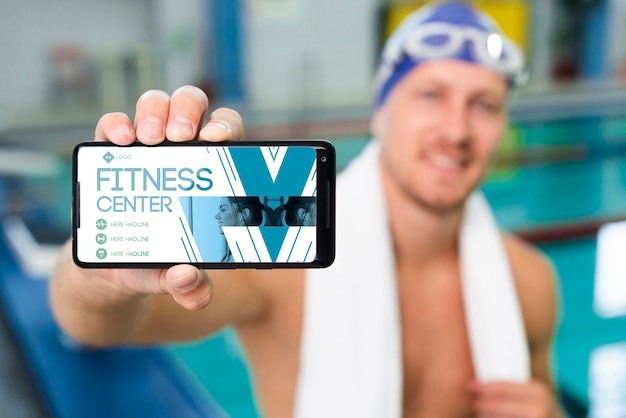 Swimmer holding a mobile phone with fitness center landing page Free Psd