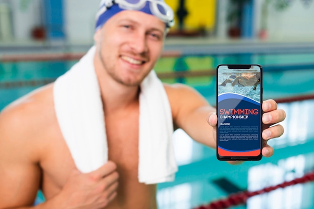 Swimmer in a pool house holding a mock-up mobile phone Free Psd