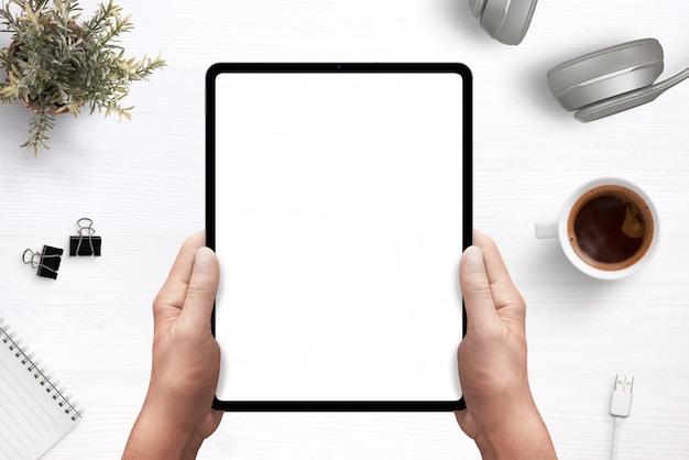Tablet in man hands mockup above work desk with separated layers for creating a scene Premium Psd