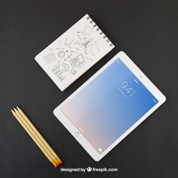 Tablet, pencils and notebook with drawing Free Psd