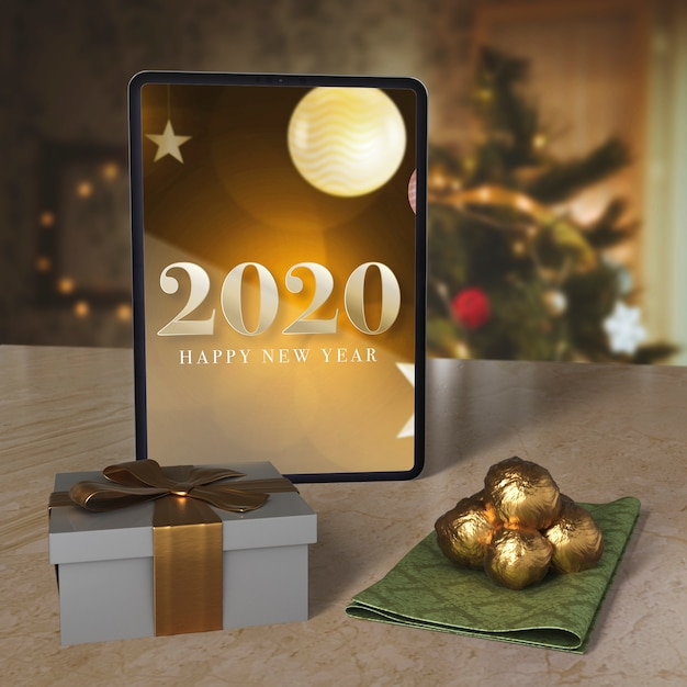 Tablet with new year wish message on table Free Psd
