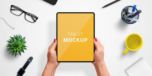 Tablet in woman hands with isolated screen for app or web site design presentation mockup. top view, flat lay composition Premium Psd