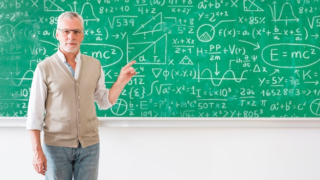 Teacher pointing at board with math formulas Free Psd