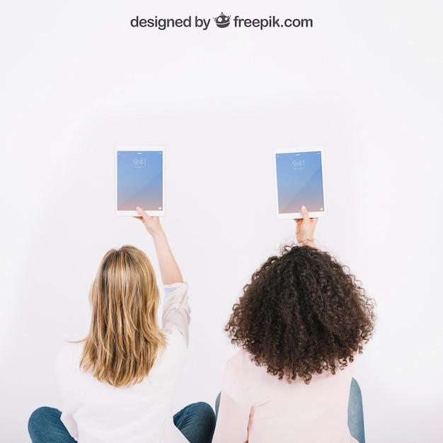 Mockup di tecnologia con donne che tengono tavoli in aria Psd Gratuite