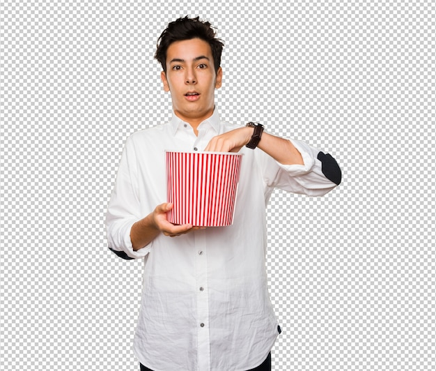 Teenager holding a popcorn bucket Premium Psd