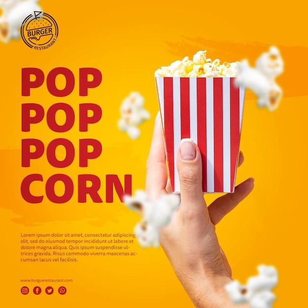 Template hand holding popcorn bag Free Psd