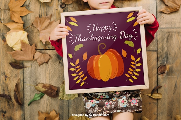 Thanksgiving mockup with girl holding frame Free Psd