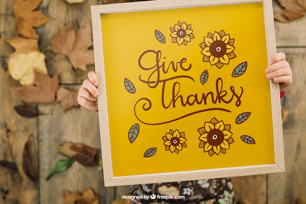 Thanksgiving mockup with kid holding frame Free Psd