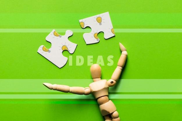 Композиция сверху с кусочками головоломки и деревянным роботом Бесплатные Psd