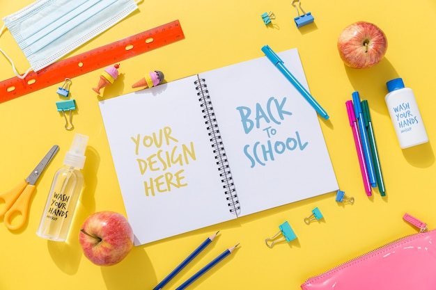 Top view of back to school notebook with pencils and apple Premium Psd