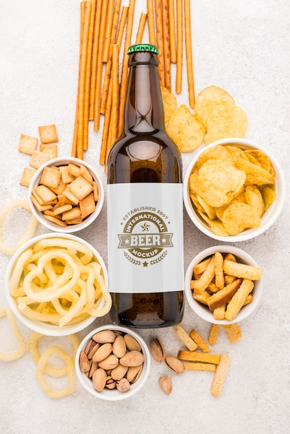 Top view of beer bottle with assortment of snacks Free Psd