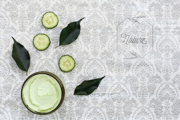 Top view of body butter and cucumber on plain background mock-up Free Psd