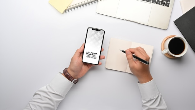 Top view of businessman hand working with smartphone mockup Premium Psd