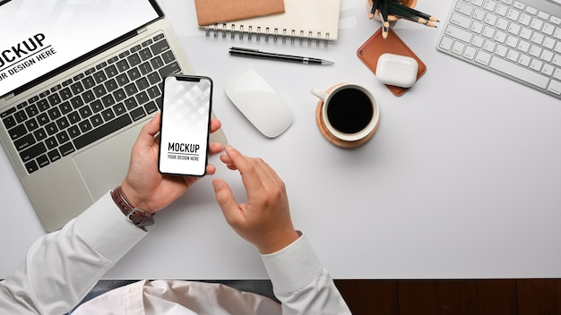 Top view of businessman hands using smartphone mockup Premium Psd