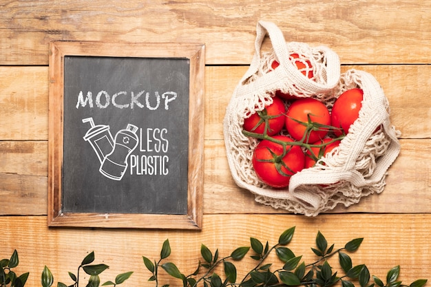 Top view of chalkboard and tomatoes in reusable bag Free Psd