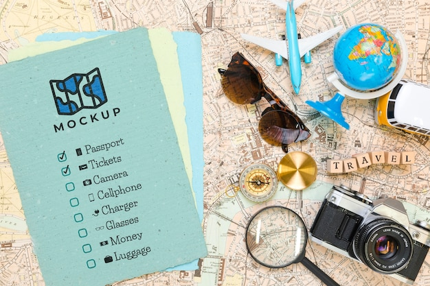 Top view of checklist with sunglasses and globe for traveling Free Psd