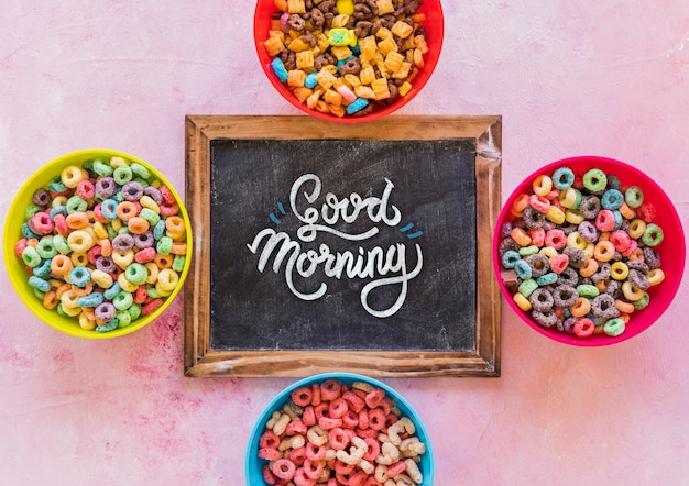 Top view of colorful cereals and chalkboard on plain background Free Psd