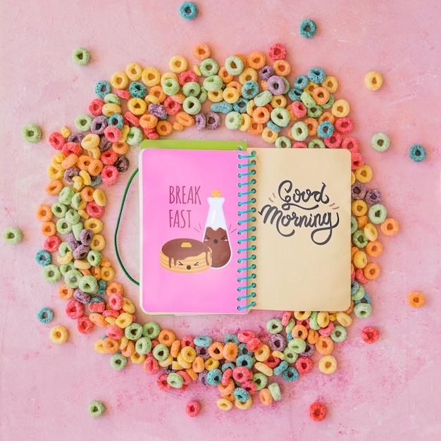 Top view of colorful cereals and notebook on plain background Free Psd