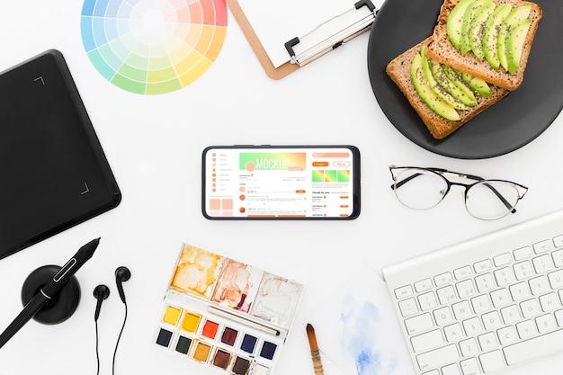 아보카도 토스트와 전화 모형을 갖춘 탑 뷰 데스크 무료 PSD 파일