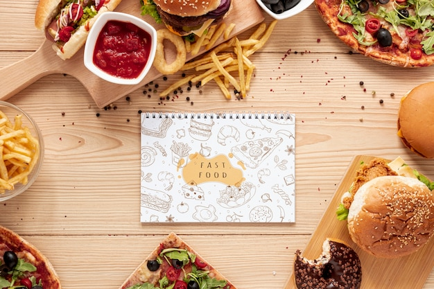 Top view of fast food on wooden table with notebook mock-up Free Psd