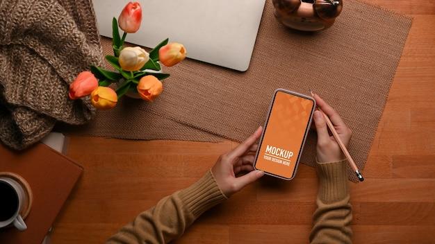 Top view of female hand using smartphone mockup with laptop and flower vase Premium Psd
