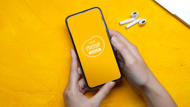 Top view of female hands holding mock up smartphone Premium Psd