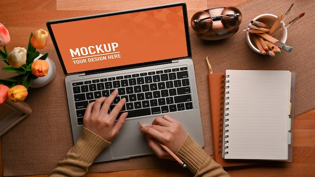 Top view of female hands typing on laptop mockup on the table with notebook Premium Psd