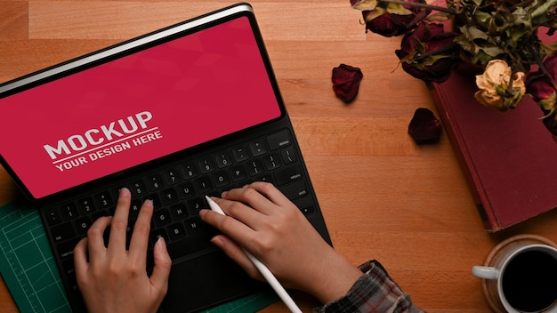 Top view of female hands typing on tablet mockup on wooden table Premium Psd