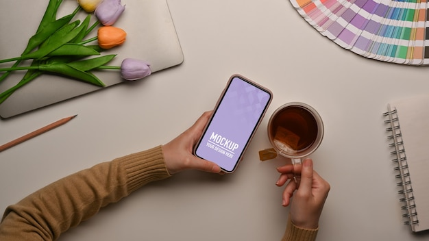 Top view of female using smartphone mockup on workspace Premium Psd