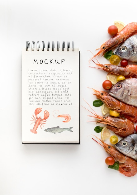 Top view of fish with shrimp and notebook Free Psd