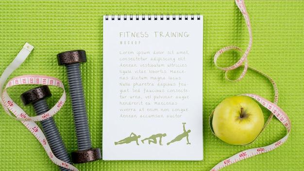 Vista dall'alto del notebook fitness con mela e nastro di misurazione Psd Gratuite