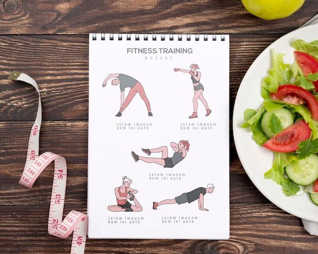 Vista dall'alto del notebook fitness con insalata e nastro di misurazione Psd Gratuite
