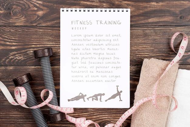 Vista dall'alto del notebook fitness con pesi e nastro di misurazione Psd Gratuite