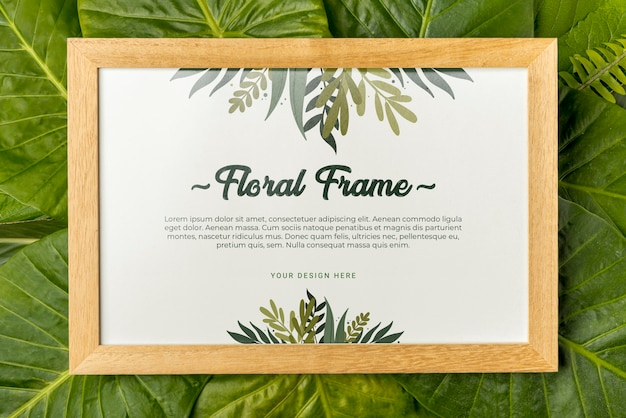 Top view floral frame surrounded by green leafs Free Psd