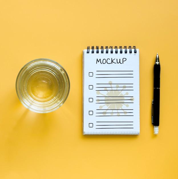 Vista dall'alto di un bicchiere d'acqua con taccuino e penna Psd Gratuite
